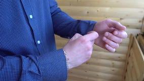 Jonge mens die op de kokers van het blauwe overhemd dichtknopen stock footage