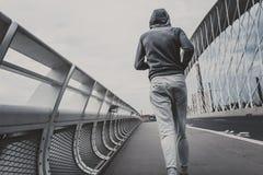 Jonge mens die op de moderne brug in de stad lopen Royalty-vrije Stock Fotografie