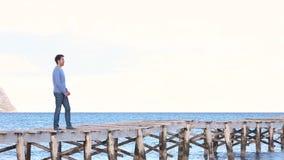 Jonge mens die op de pier blijven die zijn wapens openen stock video