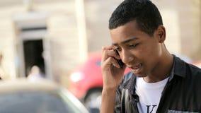 Jonge mens die op de straat glimlachen en op zijn smartphone spreken stock footage