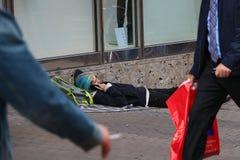 Jonge mens die op de telefoon spreken die op de straat liggen Royalty-vrije Stock Afbeeldingen