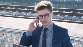 Jonge mens die op de telefoon spreken die op de trein wachten stock footage