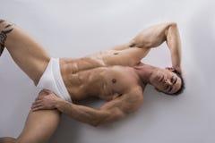 Jonge mens die op de vloer met naakt spierlichaam leggen Stock Foto