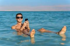 Jonge mens die op de waterspiegel van het dode overzees drijven en zijn smartphone gebruiken stock fotografie