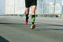 Jonge mens die op de weg van de stadsbrug lopen Marathon die in het ochtendlicht lopen Het lopen op stadsweg De voeten van de atl royalty-vrije stock afbeelding