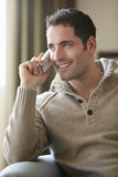 Jonge mens die op draadloze telefoon thuis spreken Stock Foto's