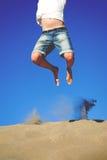 Jonge mens die op een duin springen stock foto