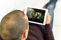 Jonge mens die op een film of op een reeks in zijn tablet letten Stock Foto's
