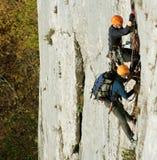 Jonge mens die op een kalksteenmuur beklimmen met brede vallei op de achtergrond Stock Foto