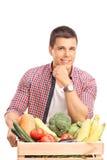 Jonge mens die op een krathoogtepunt leunen van groenten Stock Foto's