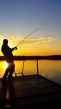 Jonge mens die op een meer bij zonsondergang vissen Royalty-vrije Stock Afbeeldingen
