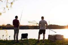 Jonge mens die op een meer bij zonsondergang vissen en van hobby genieten stock foto