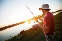 Jonge mens die op een meer bij zonsondergang vissen en van hobby genieten stock foto's
