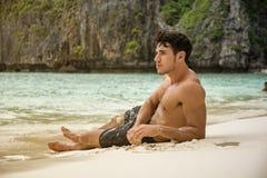 Jonge mens die op een tropisch strand liggen royalty-vrije stock afbeeldingen