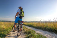 Jonge mens die op fiets in ochtendzonsopgang reizen met prachtig Royalty-vrije Stock Fotografie
