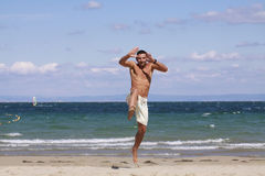 Jonge mens die op het blauwe strand springen. Royalty-vrije Stock Foto's