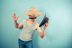 Jonge mens die op hoeden proberen Stock Fotografie