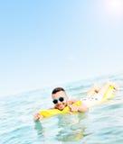 Jonge mens die op matress zwemmen Stock Foto's