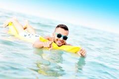 Jonge mens die op matress zwemmen Stock Afbeelding