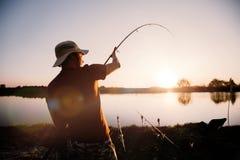 Jonge mens die op meer bij zonsondergang vissen die van hobby genieten stock afbeelding