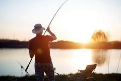 Jonge mens die op meer bij zonsondergang vissen die van hobby genieten stock fotografie