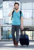 Jonge mens die op mobiele telefoon met zak spreken Stock Afbeeldingen