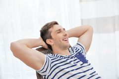 Jonge mens die op moderne stoel met handen achter zijn hoofd rusten Stock Foto's