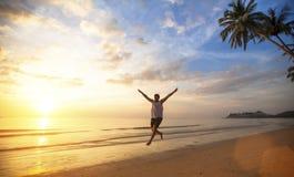 Jonge mens die op oceaankust tijdens verbazende zonsondergang springen Royalty-vrije Stock Foto's