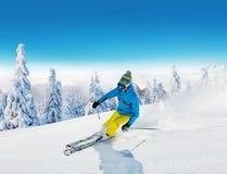 Jonge mens die op piste ski?en stock afbeelding