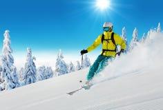 Jonge mens die op piste ski?en stock fotografie