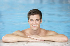 Jonge Mens die op Rand van Zwembad rust Royalty-vrije Stock Afbeeldingen