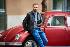 Jonge mens die op rode retro auto met fotocamera leunen royalty-vrije stock fotografie
