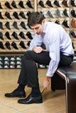 Jonge mens die op schoenen proberen Stock Afbeeldingen