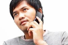 Jonge mens die op slimme telefoon thuis spreken Royalty-vrije Stock Foto