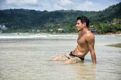 Jonge mens die op strand door de oceaan leggen royalty-vrije stock afbeelding
