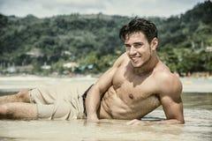 Jonge mens die op strand door de oceaan leggen royalty-vrije stock foto's