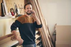 Jonge mens die op telefoon in zijn workshop spreken royalty-vrije stock foto's