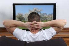 Jonge mens die op TV letten Stock Foto
