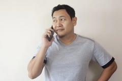 Jonge Mens die op zijn Telefoon, het Gelukkige het Glimlachen Lachen spreken royalty-vrije stock afbeelding