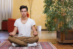 Jonge mens die op zijn woonkamervloer mediteren Stock Foto's