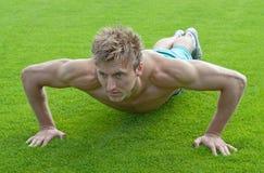 Jonge mens die opdrukoefeningen op groen gras doet Stock Afbeeldingen