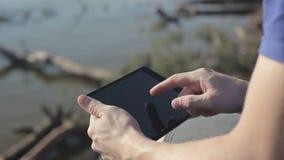 Jonge mens die in openlucht met tablet werken stock videobeelden
