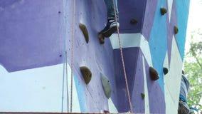 Jonge mens die openluchtmuur beklimmen voorraad De mens praktizeerde op de het beklimmen muur stock video