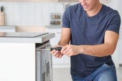 Jonge mens die oven herstellen, stock afbeelding
