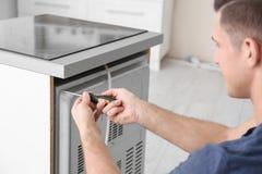 Jonge mens die oven herstellen, stock fotografie