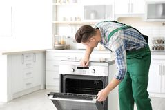 Jonge mens die oven herstellen stock foto