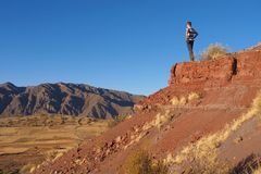 Jonge mens die over droog en leeg landschap in Bolivië letten op stock foto
