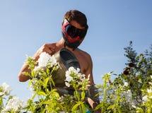 Jonge mens die in paintballmasker de bloemen water geven Stock Foto