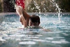 Jonge mens die in pool zwemt Stock Afbeeldingen