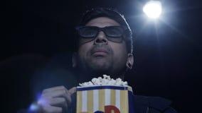 Jonge mens die popcorn in een filmtheater eten stock video